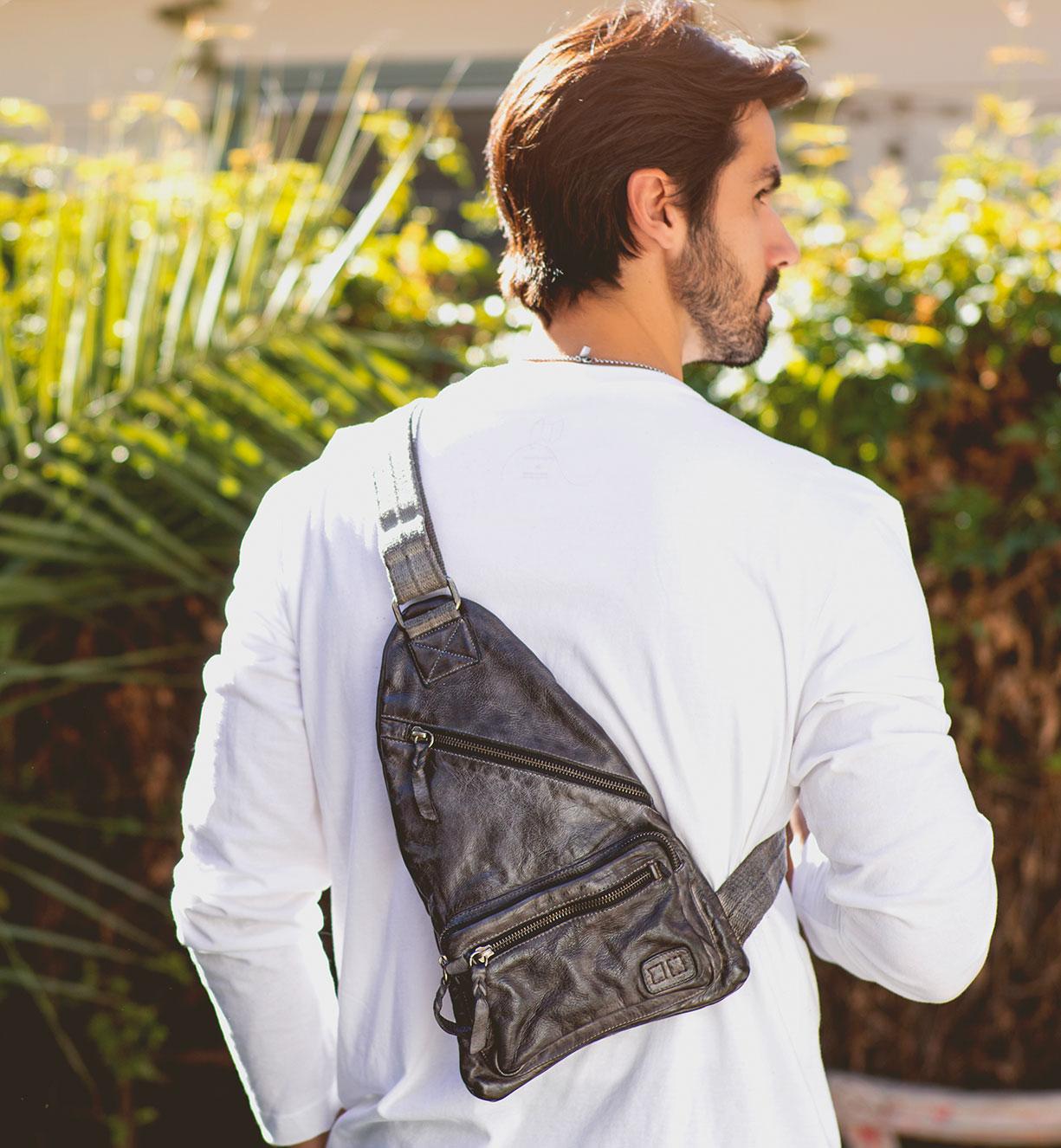 Men is carrying over the right shoulder black leather handbag