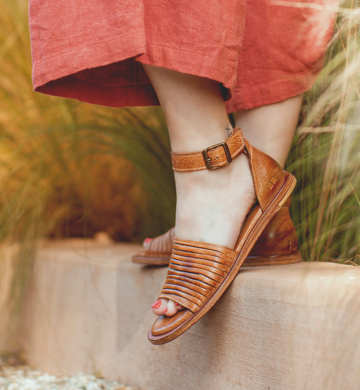 Woman is wearing summer sandals in tan color