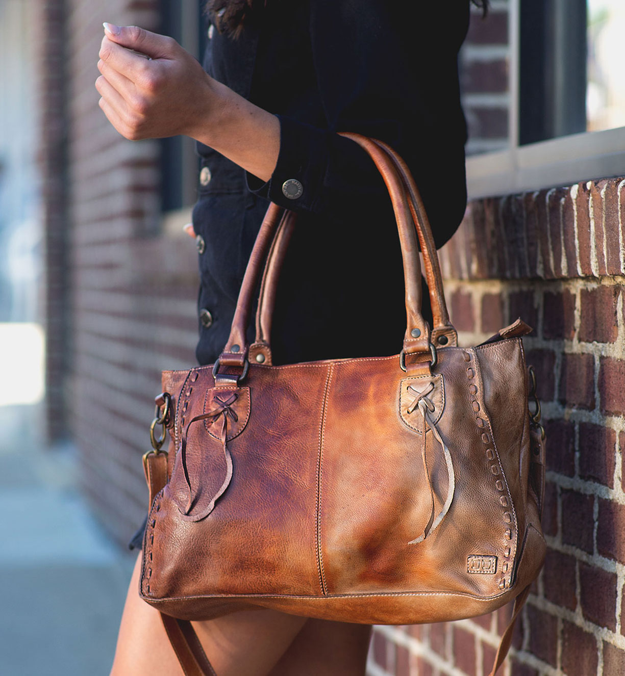 Woman is holding a handbag in her hand