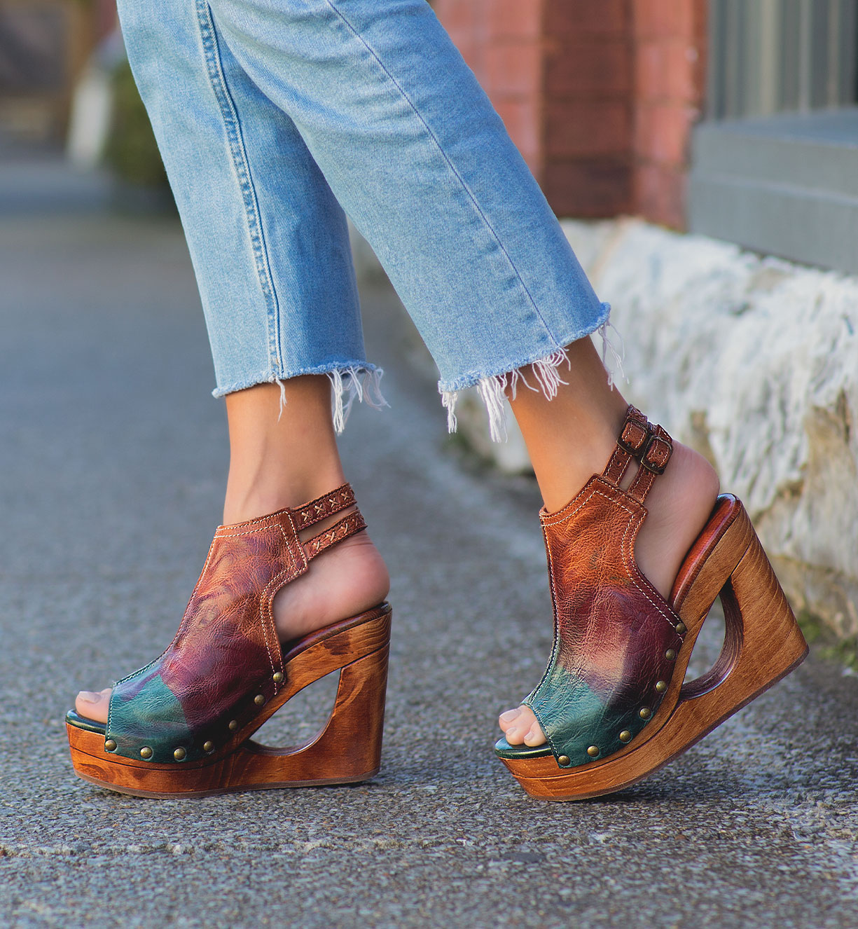 Woman's foot wearing color blocking leather heels wedges