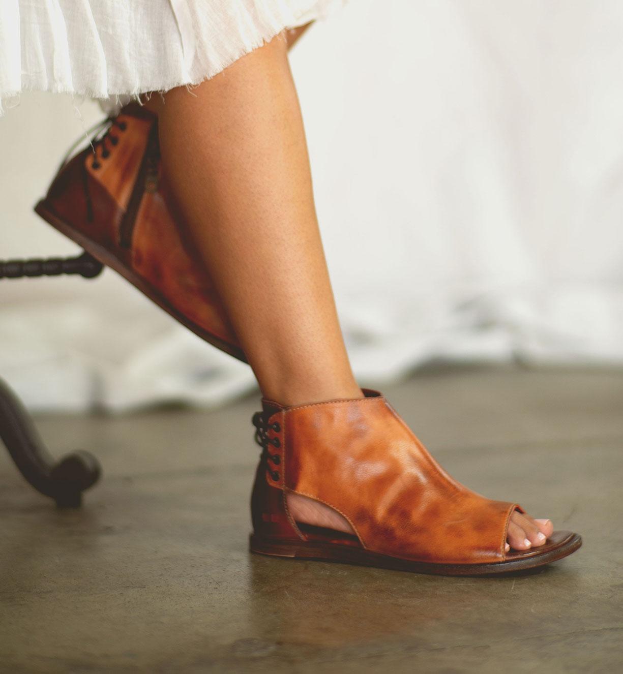 Woman's foot wearing tan leather open toe sandal