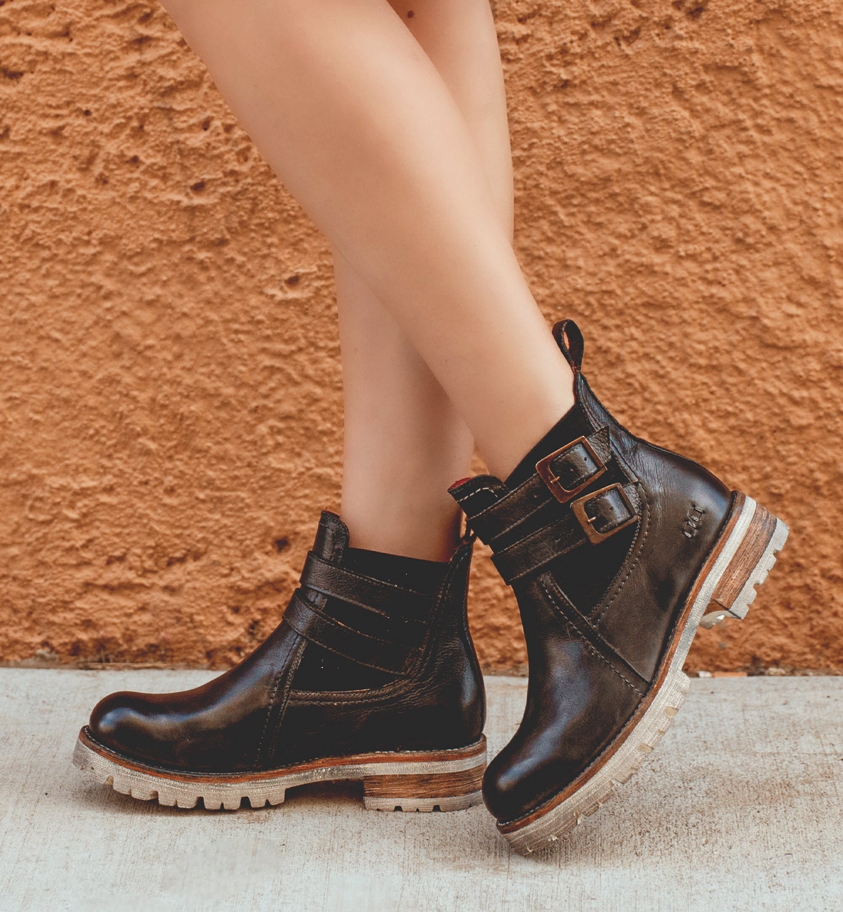 Women feet featuring lace up black short boots on lightweight platform