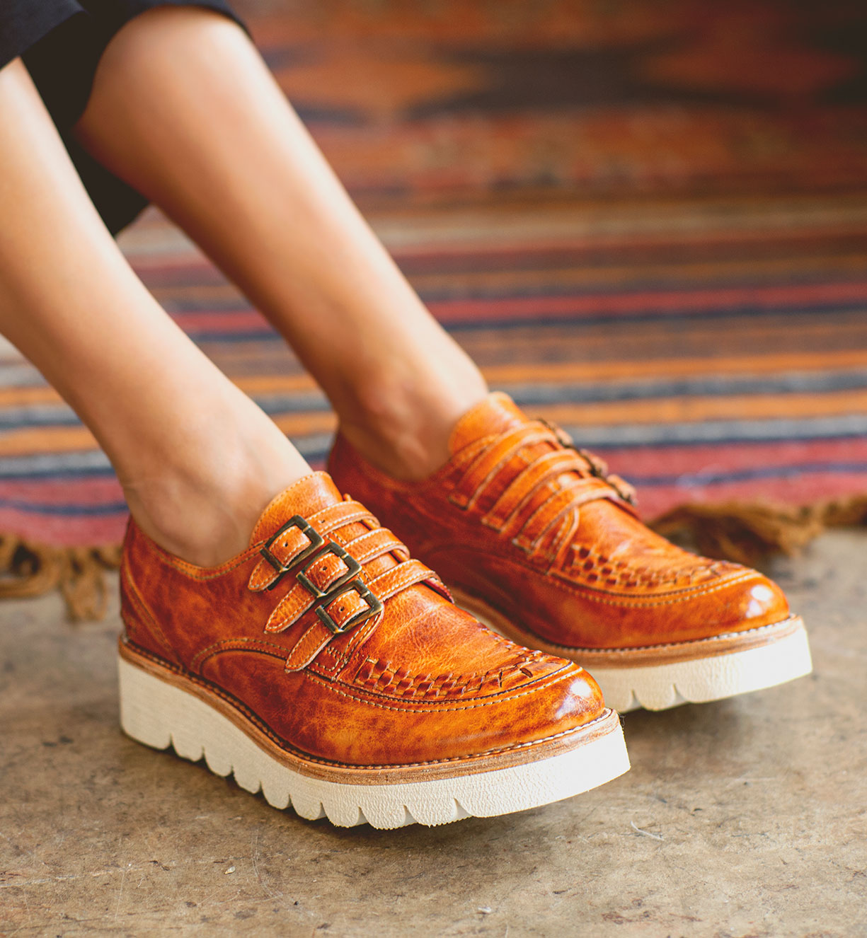 Woman's foot wearing tan leather paltform shoes