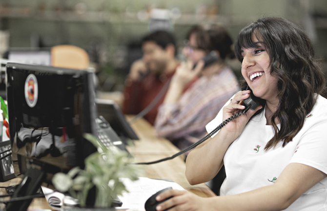 Smiling Elsa from Customer Service and her team mates on the phone in front of computers