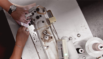 Top view of worker at a leather sewing machine stitching