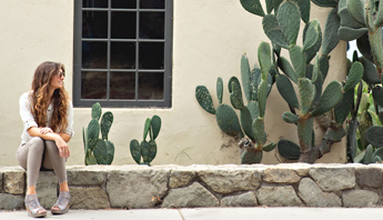 Women wearing the Grey Jacey leather platform sandal sitting on a stone wall looking towards cacti