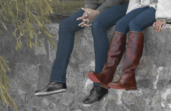 Legs of a couple sitting on a wall wearing Black leather sneakers and tall dark scarlet Manchester leather boots