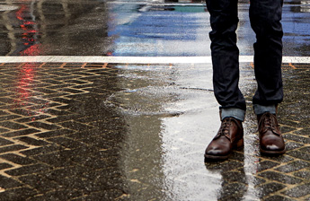Legs of man standing on wet concrete wearing rolled up denim and Teak Leather Bradley Goodyear welted mens chukka boots