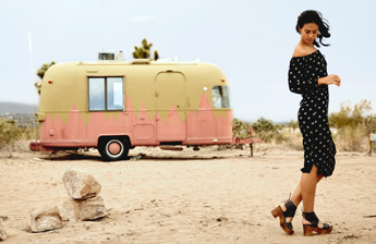 Woman with vintage trailer in back wearing black back laced wood platform leather Mali Sandal