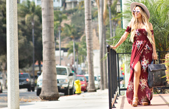 Woman in long red dress holding Navy Vegetable tanned leather backpack Howie looking out across palm tree lined streets