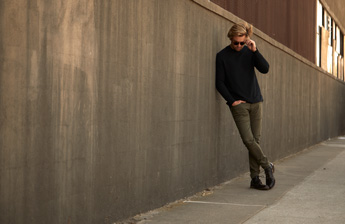 man wearing a sweater, jeans & leather shoes leaning against a long cement wall.