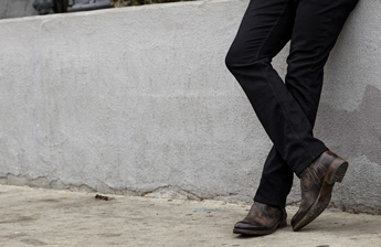 A man wearing dark denim jeans wearing BedStü's Otto boot, leaning up against a low cement wall.