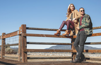 A woman sitting on a wooden railing wearing a tan peacoat over a grey sweater, maroon leather leggings, and Bedstu's Yell P short boots, next to a man standing, leaning against the wooden railing wearing sunglasses, a camouflage jacket, maroon t-shirt, and black denim jeans, with Bedstu's Otto boots.