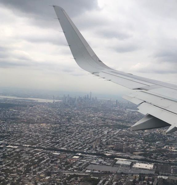 Aerial shot of NYC from a plane window, with the plane wing in the shot