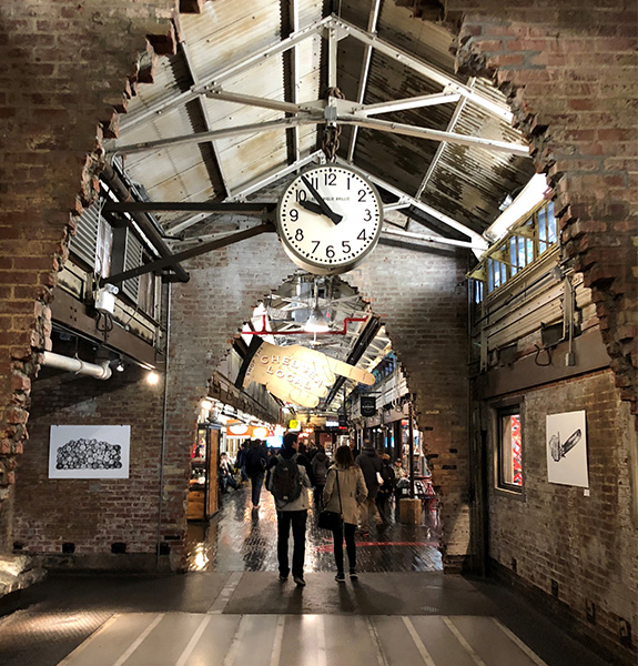 Image of the inside of Chelsea Market in NYC, with people walking under old brick archways with a large antique clock hanging from the ceiling