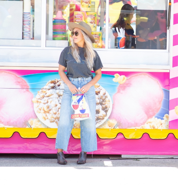Woman wearing Bed Stu Copper booties with loose light wash jeans and a t-shirt, standing in front of a brightly colored food stand