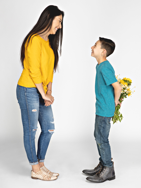 Brunette Mom wearing yellow sweater, distressed jeans and BEDSTU Las Cruces woven leather huarache sandals, standing with young son wearing teal t-shirt, jeans and oversized BEDSTU leather mens boots.