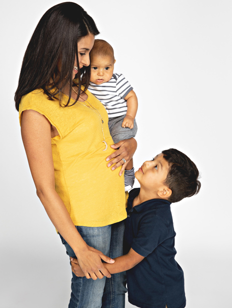 Brunette mom smiling, looking down at son, wearing yellow top and dark jeans, holding baby in one hand and toddler is looking up at her holding her legs.
