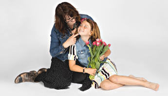 Wide shot of auburn haired mom sitting on the ground with young daughter wearing jean jacket, black and white skirt and BECCA womens distressed black leather bootie, daughter is holding pink tulips and looking at her lovingly, wearing jean vest and striped dress.