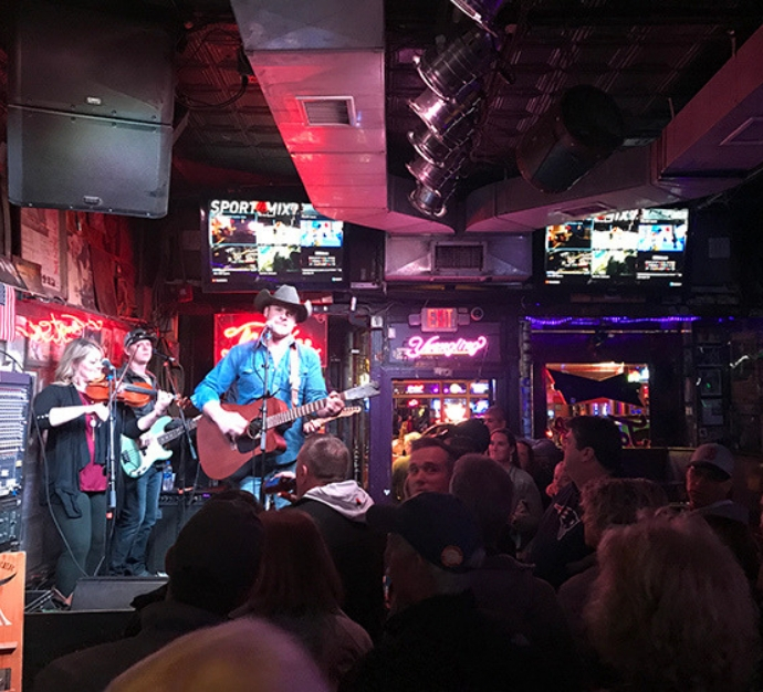 Close shot of a man performing with a guitar on stage in a bar in Nashville, with people crowded around to watch