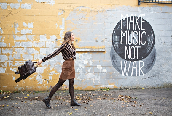 Woman walking by a wall with chipped yellow paint that says, 'make music not war', wearing Bed Stu Winslet boots and swinging a leather bag