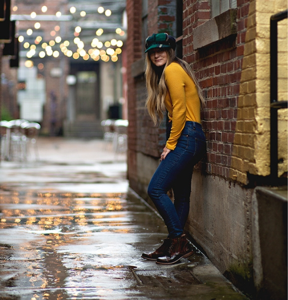 Woman standing against a brick wall in a wet alleyway wearing Bed Stu Bonnie boots, with twinkle lights strung up in the background