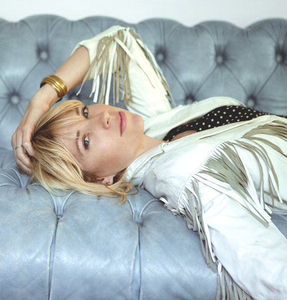 Southern California-based singer/songwriter Brooke White wearing a white leather fringe jacket in her home.