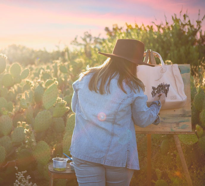 Sarah paints a ROCKAWAY bag in a field at sundown