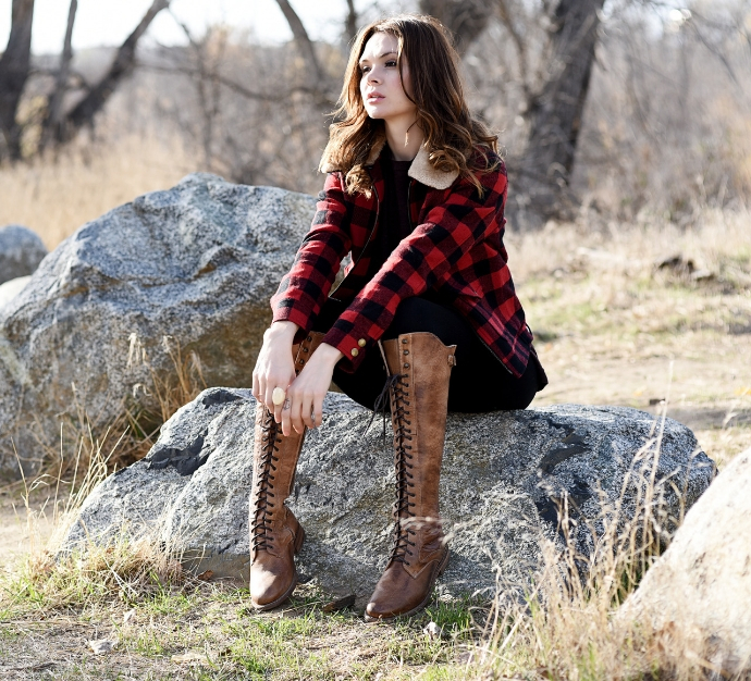 Woman sitting on a rock wearing Bed Stu Della boots and a plaid long sleeve shirt, staring off in the distance