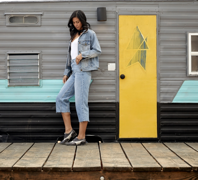 Woman standing up against a trailer with a yellow door, wearing all denim and Bed Stu Shaula Oxfords in Black Driftwood Nectar Lux color