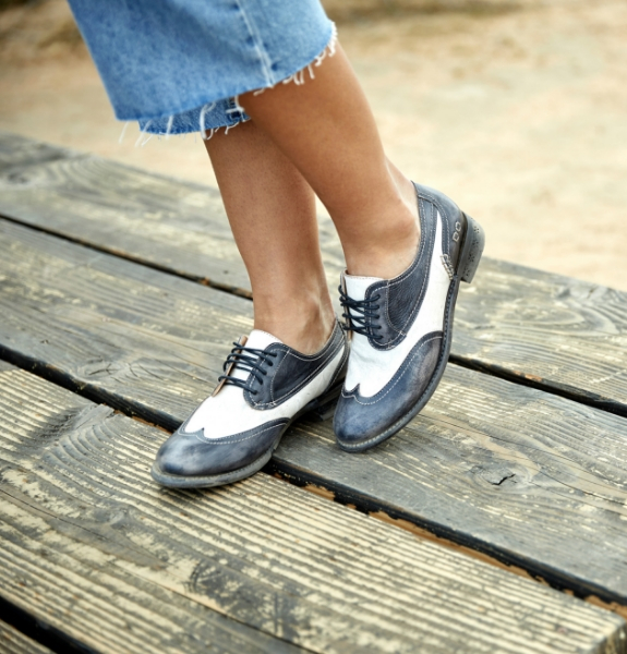 Close shot of a woman wearing loose cutoff jeans wearing two toned black and white Bed Stu Shaula Oxfords