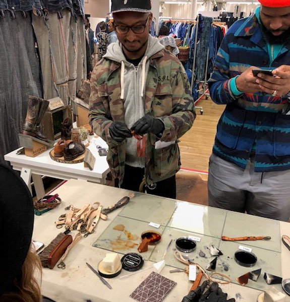 Man wearing gloves dying leather key chains at NYC Denim Days