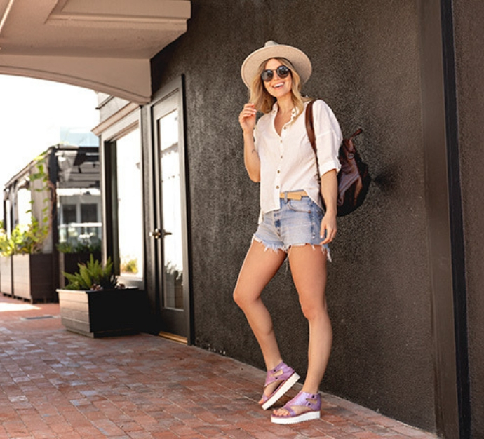 Woman standing on a brick walkway wearing jean shorts, a white blouse, a hat, and Bed Stu Soni sandals in a metallic purple color