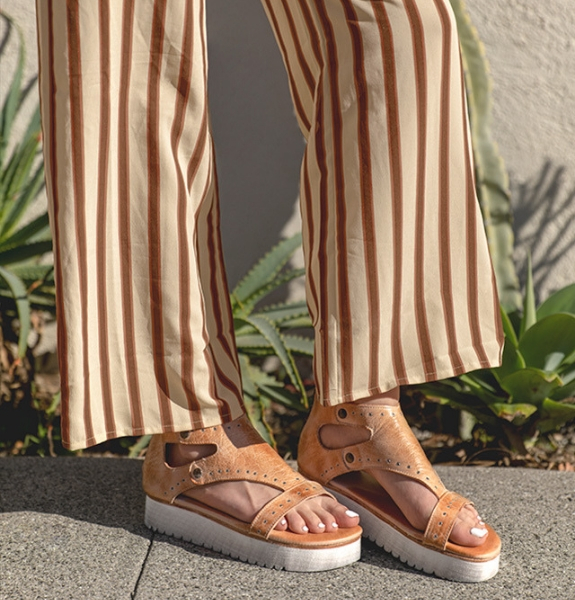 Close shot of woman wearing striped pants with Bed Stu Soni sandals in Bone Rustic