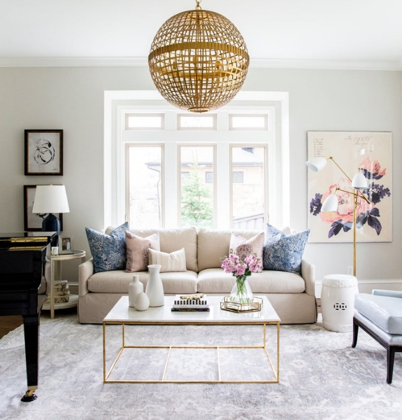 Image of a white and gold themed living room neatly organized with a glass coffee table and a gold decorative orb light hanging above