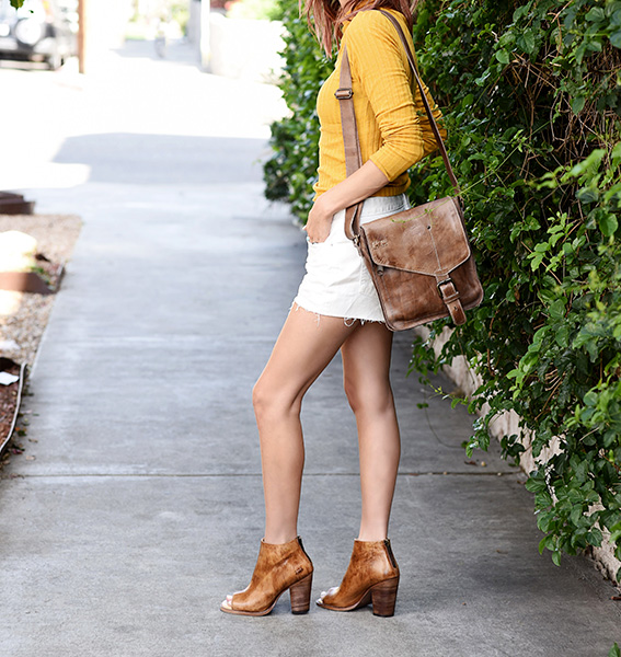 Woman standing next to a green plant wall wearing a tight yellow blouse, white mini skirt, Bed Stu Onset heels in Tan Driftwood, and Venice Beach bag in Tan