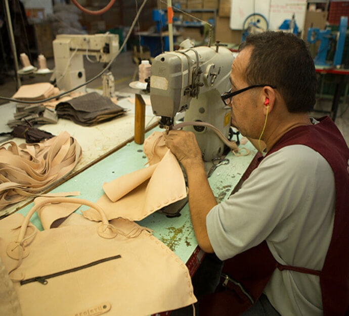 Top shot of a worker in a factory assembling a leather Bed Stu Rockaway bag using a sewing machine