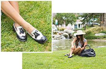 Close shot and wide shot of a woman sitting on grass in front of a pond wearing two toned Bed Stu Capella loafers with a black Rockaway bag