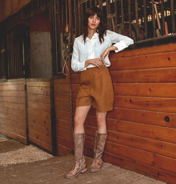 Bed|Stü's handmade leather mid-calf boot, Endless in Tan MD, modeled with brown culotte shirts and a white flowy blouse.