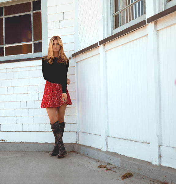 Bed|Stü's handmade leather tall boot, Midge in Black MD Rust BFS, modeled with a red A-line skirt and black long sleeve top.