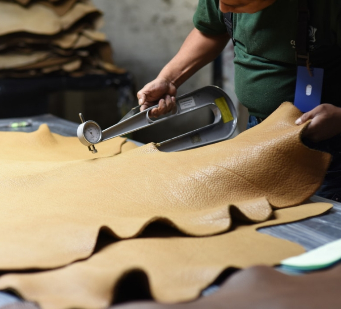 Worker in a factory measuring the thickness of a leather hide using a metal tool