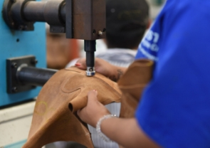 Close shot of a factory worker using a machine to smooth a part of a leather hide