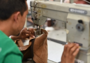 Close shot of a worker using a sewing machine to stitch two ends of a leather piece together