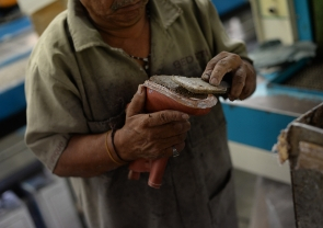 Close shot of a worker using a wooden plank to apply a cork and leather mixture to the midsole of a Goodyear Welted shoe
