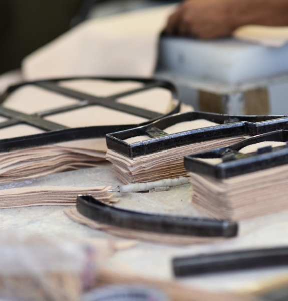 Close shot of several stacks of thin leather pieces stacked up with cutting dies laying on top of them