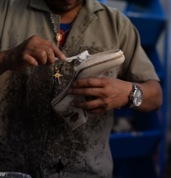 Close shot of a factory worker using a toothbrush to apply water based glue to the edge of the midsole of a shoe