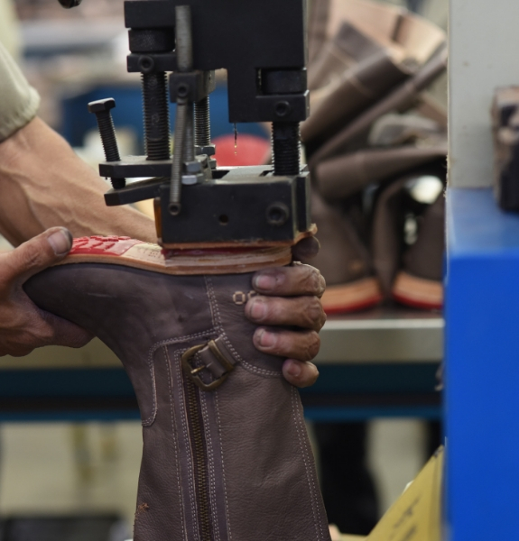 Tight shot of a man using a machine to adhere the heel of a leather boot to the rest of the outsole