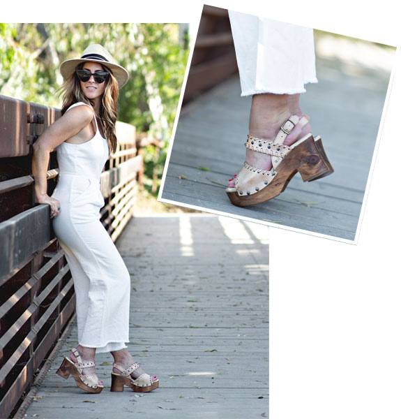 Images of a woman standing against a railing on a bridge, wearing a white romper and Bed Stu Kampala wooden heels in Bone Mason