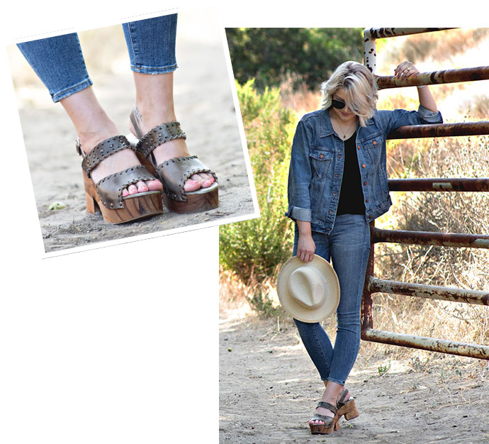 Images of a woman standing in dirt holding onto a rusty metal fence, wearing all denim and Bed Stu Kampala wooden heels in Taupe Rustic