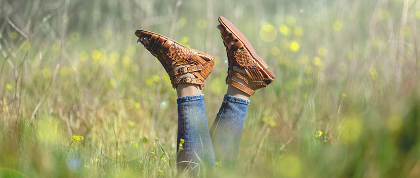 Tight shot of tan leather huarache style sandals in a green field with yellow flowers.